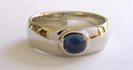 custom engagement ring with oval sapphire cabochon set in white gold